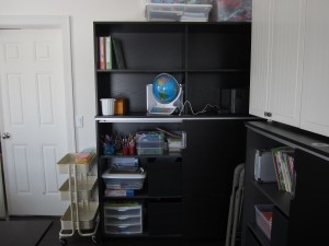 Sliding doors  are open to show the shelves.  See the black cubes in there?  Hidden kid art stuff!  Also, that rolling cart to the left.  You got it.  It's from Ikea.  It's working great for current kid projects...move it out to the big kitchen table, move it back...whatever you want!